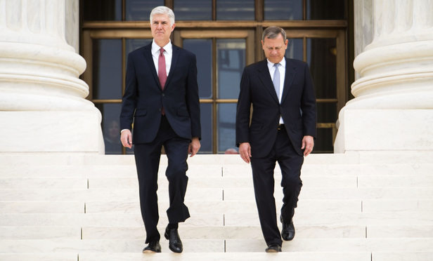 Associate Justice Neil Gorsuch, left, and Chief Justice John Roberts Jr., right, walk down the steps of the U.S. Supreme Court after holding an Investiture ceremony for Justice Gorsuch, on June 15, 2017.