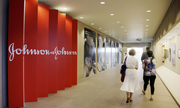 People walk along a corridor at the headquarters of Johnson & Johnson in New Brunswick, N.J., on July 30, 2013.