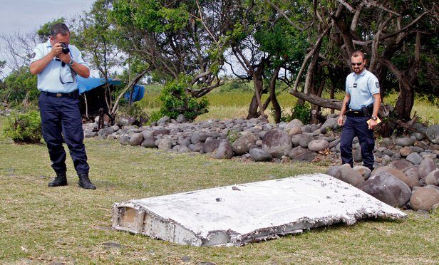 French police officers look over a piece of debris from a plane in Saint-Andre, Reunion Island, on July 29, 2015. The wing was later found to be from missing Malaysia Airlines Flight 370 that went missing March 8, 2014, with 239 people aboard while flying from Kuala Lumpur to Beijing.