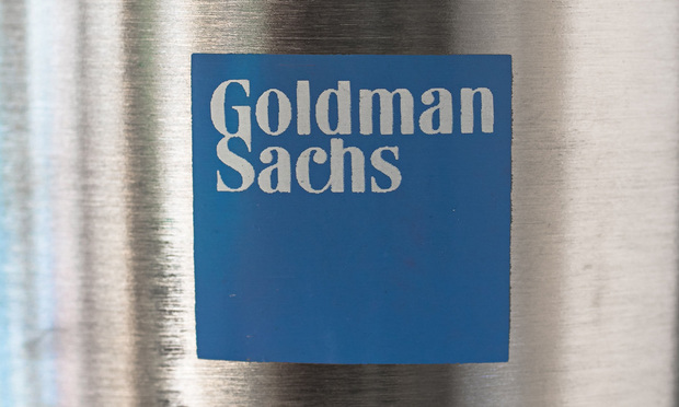 A blue logo of Goldman Sachs on a metallic convex surface.