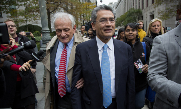 Rajat Gupta, center right, leaves federal court in New York, Wednesday, Oct. 24, 2012 after the former Goldman Sachs and Procter & Gamble Co. board member was sentenced Wednesday to 2 years in prison for feeding inside information about board dealings with a billionaire hedge fund owner who was his friend. At left is Gupta's attorney, Gary Naftalis. (AP Photo/Craig Ruttle)