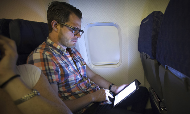 A passenger uses a tablet on a plane equipped with Gogo Inflight Internet service, whose term of use contract is being challenged in the Eastern District.