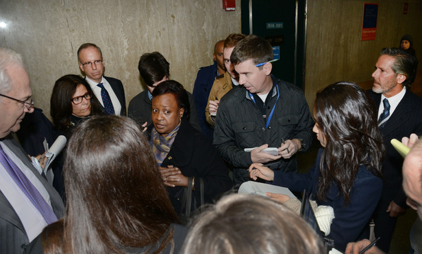 Dewey juror Edith Hines talk to reporters and defense attorneys outside the courtroom after a mistrial was declared Monday. Defendants Steven Davis, third from left, and Stephen DiCarmine, at right, listen in.