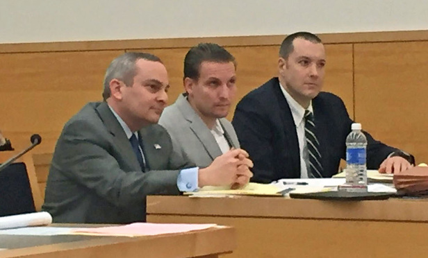 John Giuca, seated at the defense table, center, was convicted in 2003 of the murder of Mark Fisher. Seated with Giuca are his attorneys, Mark Bederow, left, and Andrew Stengel.