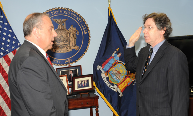 Daniel Master Jr., right, is sworn in as Acting District Attorney of Staten Island by Richmond County First Deputy Clerk Mario DiRe.