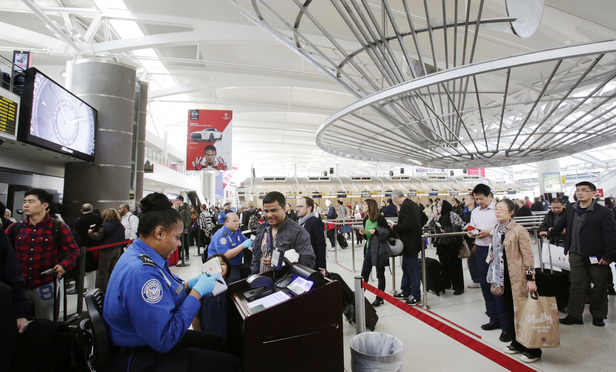 A TSA officer, left, checks a passenger's ticket, boarding pass and passport at John F. Kennedy International Airport.