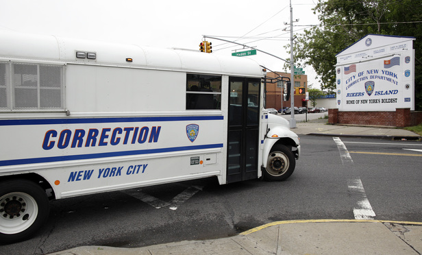 A sign greets people arriving on a Department of Correction bus at Rikers Island.