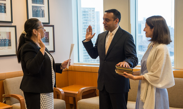Sanket Bulsara, center, is sworn in by Eastern District Chief Judge Dora Irizarry as a magistrate judge on August 28. He is the first South Asian-American to serve on the bench in the Second Circuit. His wife, Christine DeLorenzo, is at right.