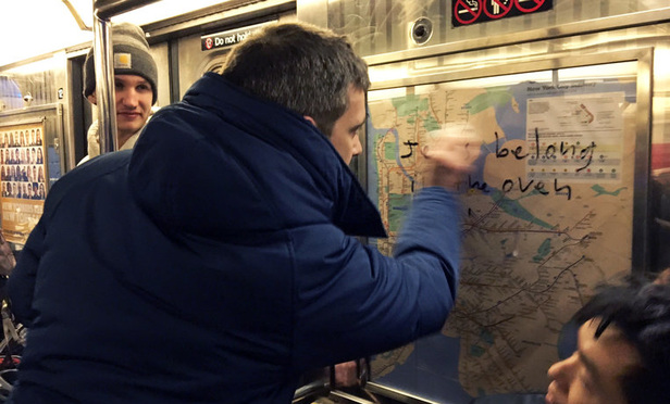New York City subway riders remove anti-Semitic graffiti.