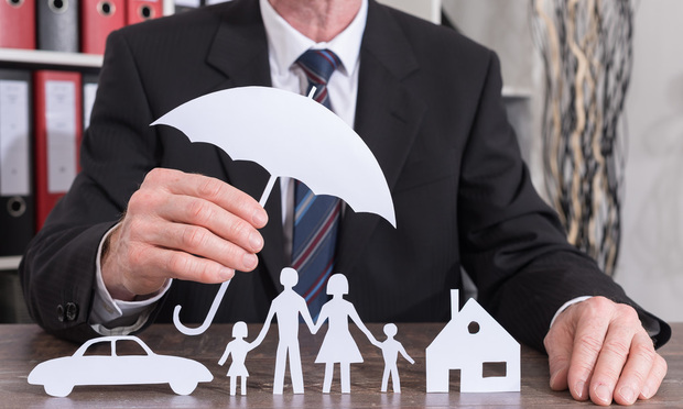 House, car and family protected with an umbrella by an insurer - insurance concept