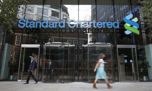 Pedestrians pass the entrance to Standard Chartered Plc's headquarters in London, U.K., on Tuesday, Aug. 14, 2012. Standard Chartered Plc rose as much as 5.1 percent in London after the bank settled a money-laundering probe for $340 million the day before it was due to appear at a hearing to defend its right to operate in New York. Photographer: Simon Dawson/Bloomberg