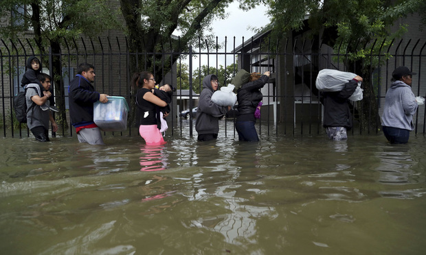 Residents from Bayou Parc at Oak Forest carry their belongings while evacuating the apartment complex during the Tropical Storm Harvey, Sunday, Aug. 27, 2017, in Houston.
