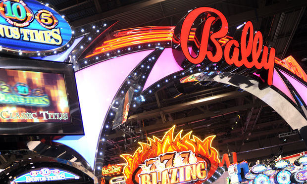 Attendees visit a Bally Technologies Inc. booth in the Las Vegas Convention Center.