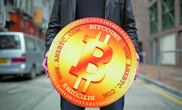 A man poses for a photograph with a mock Bitcoin outside the ANXBTC store in Hong Kong, China.
