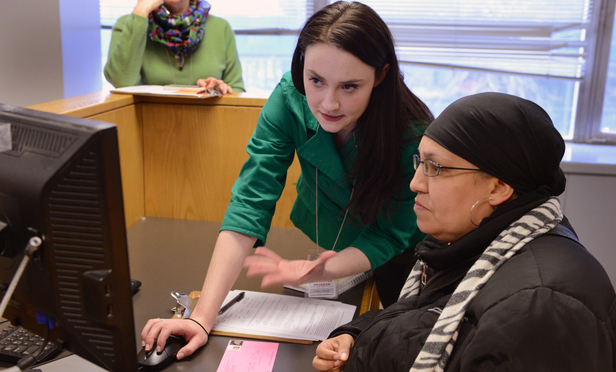 Caitlyn Brady, left, a navigator in Brooklyn Housing Court, helps Angela Caceres.