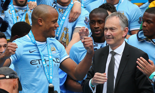 Premier League Cheif Executive Richard Scudamore looks on as Vincent Kompany of Manchester City celebrates with his team-mates after the Barclays Premier League match between Manchester City and West Ham United at the Etihad Stadium on May 11, 2014 in Manchester, England.