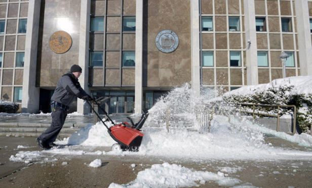 The courtyard of Nassau Courthouse being cleared of snow