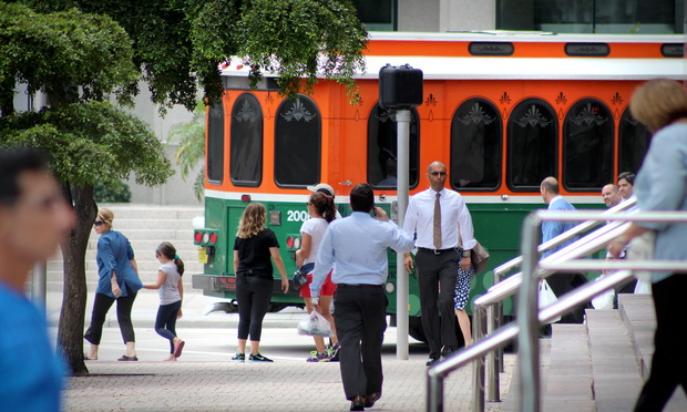 Pedestrians walk on Biscayne Blvd as the Miami Trolley makes a to SE 2nd St in Downtown Miami.