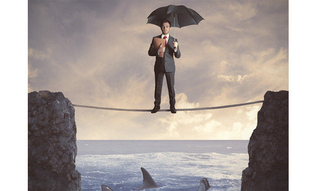 man standing with umbrella on tightrope over sharks