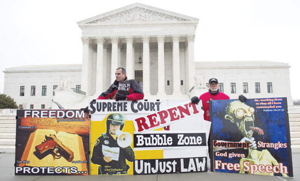 Pro-life demonstrators stand outside the US Supreme Court following oral arguments in the case of McCullen v. Coakley.