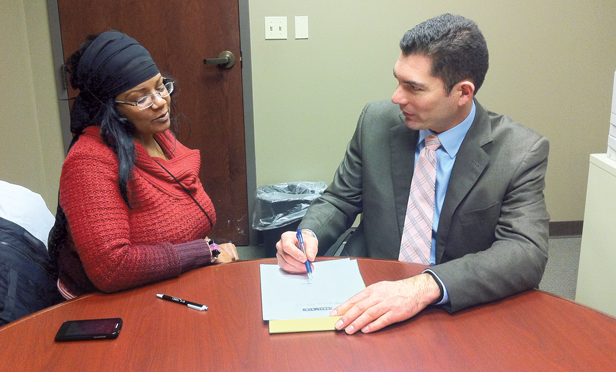 Attorney Paul Zindle counsels client Clarissa Muhammad at Community Legal Aid Services, Inc., in Akron, Ohio.