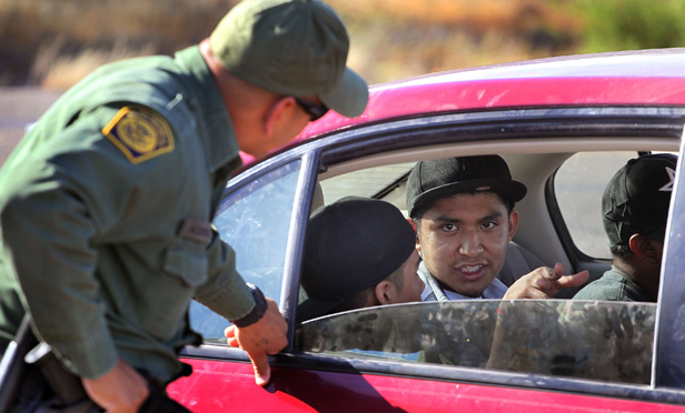 A border patrol agent checks a vehicle for people who are in the U.S. illegally.