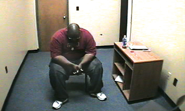 Adrian Thomas waits alone in the interrogation room of the Troy police station